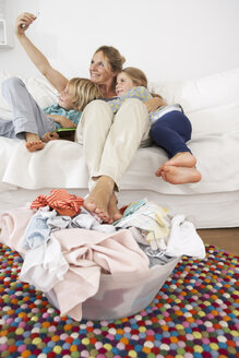 Mother, daughter and son on couch taking a selfie with laundry basket on floor - FSF000264