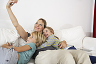Happy mother, daughter and son on couch taking a selfie - FSF000286