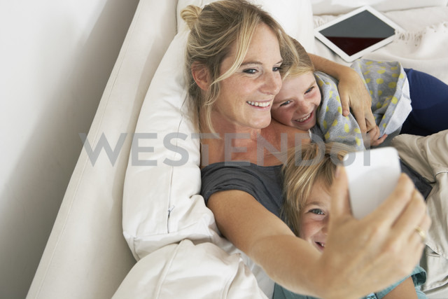 Happy mother, daughter and son on couch taking a selfie - FSF000267 - Sandra Bielmeier/Westend61
