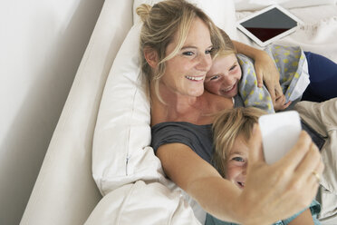 Happy mother, daughter and son on couch taking a selfie - FSF000267
