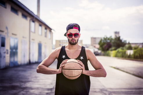 Portrait of young man with basketball wearing basecap and sunglasses - DAWF000168