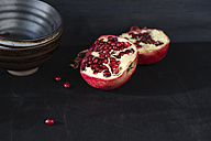 Bowl and two halves of a pomegranate on black ground - MYF000643