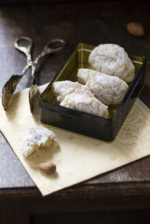 Cookie tin of Ricciarelli and pastry tong on napkin and dark wood - MYF000645