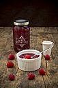 Glass and bowl of red fruit jelly, milk and raspberries on dark wood - LVF002069