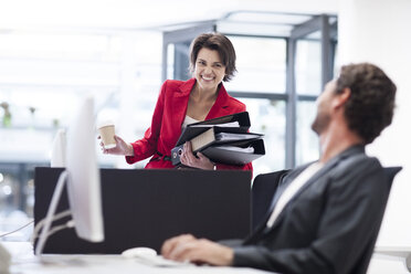 Businesswoman in office with file folders looking at colleague - ZEF007942