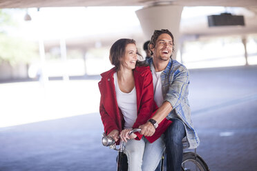 Happy couple riding bicycle in parking garage - ZEF007945