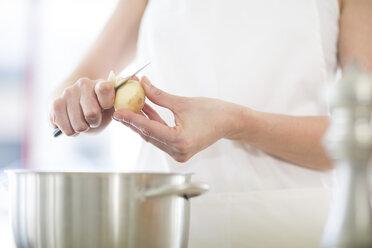 Woman peeling potatoes - ZEF007957