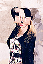 Young blond woman hiding face behind her wallet - DAWF000213