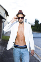 Young man wearing hat, sunglasses and white jacket on bare chest - DAWF000229