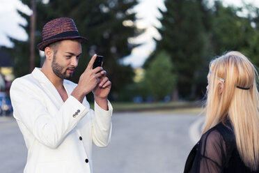 Stylish young man taking a photo of his girlfriend with smartphone - DAWF000231