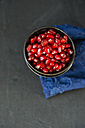 Metal bowls of pomegranate seeds on blue cloth and grey ground - MYF000654