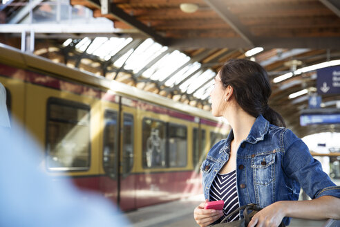 Germany, Berlin, young woman watching city train - FK000748