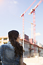 Germany, Berlin, young woman in front of construction site - FKF000710