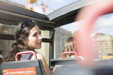 Germany, Berlin, young female tourist on city trip in a tour bus - FKF000754