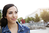 Germany, Berlin, portrait of smiling young woman on city trip - FKF000713