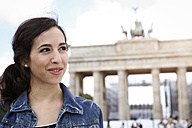 Germany, Berlin, portrait of young female tourist on city trip in front of Brandenburg Gate - FKF000715