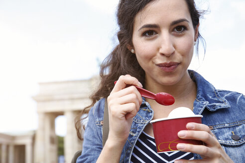 Germany, Berlin, portrait of young female tourist eating ice cream near Brandenburg Gate - FKF000721