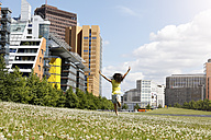 Germany, Berlin, happy young woman running on a meadow near Potsdam Square - FKF000739