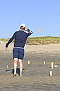 Man playing Kubb on the beach - LAF001192