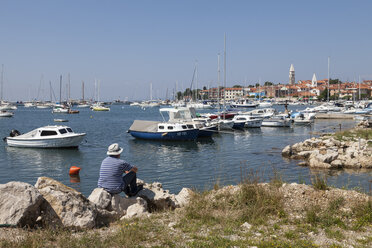 Slovenia, Istria, Izola, man at seashore with marina - WIF001141