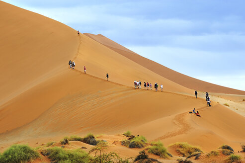 Namibia, Sossusvlei, tour group climbing on dessert dune - MBF001218