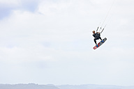 France, Bretagne, Finistere, man up in the air with his kiteboard - LAF001148