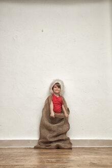 Little boy wearing Christmas cap standing in gunny bag - MMFF000401