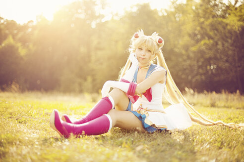 Woman wearing costume of Pretty Guardian Sailor Moon sitting on a meadow - AFF000100