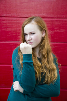 Portrait of teenage girl showing fist in front of red wooden wall - SARF000960