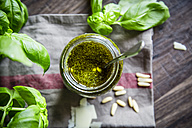 Glass of homemade pesto Genovese, pine nuts, basil leaves and parmesan on kitchen towel - SARF000944