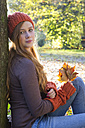 Portrait of teenage girl wearing wool cap and gauntlets leaning at tree - SARF000956