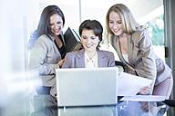Three businesswomen with laptop in office - ZEF002163