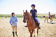 Coach and girl on horse on riding ring - ZEF001874