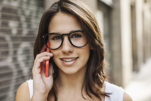 Portrait of smiling young woman telephoning with smartphone - EBSF000306