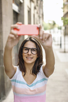 Portrait of smiling young woman taking a selfie with smartphone - EBSF000309