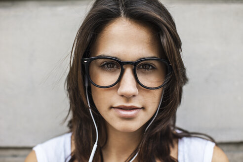 Portrait of young woman with ear phones wearing black glasses - EBSF000320