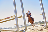 Girl with horse on show jumping course - ZEF001730