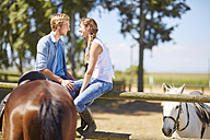 Smiling young couple with horses on paddock - ZEF001744