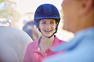 Smiling girl with braces wearing riding helmet - ZEF001754