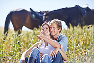 Young couple sitting in field with horses in background - ZEF001761