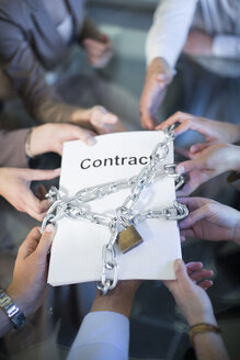 Businesspeople holding contract locked with chain - ZEF002231