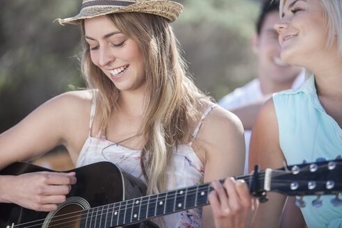 Happy friends with guitar outdoors - ZEF002448
