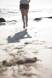 Legs of young woman running on beach - ZEF002470