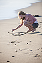 Young woman drawing heart in sand on the beach - ZEF002479