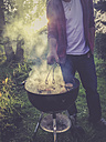 Germany, Man with kettle barbecue in garden - LVF002107