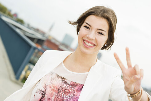 Portrait of smiling young woman showing victory sign - UUF002343