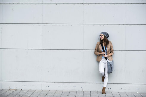 Young smiling woman leaning against a wall waiting - UUF002369