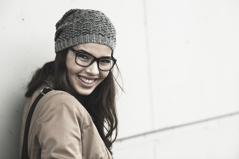 Portrait of smiling young woman wearing glasses and wool cap - UUF002379