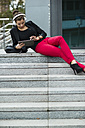 Young woman with headphones sitting on stairs using digital tablet - UUF002402