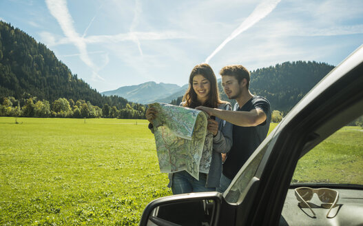 Austria, Tyrol, Tannheimer Tal, young coupe at car looking at map - UU002416